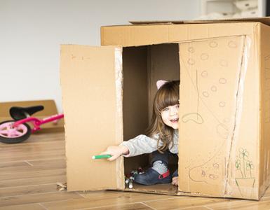Petite fille qui joue, cachée dans un carton