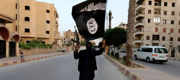a-member-loyal-to-the-isil-waves-an-isil-flag-in-raqqa_4945617